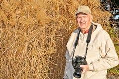 Uomo maggiore attivo con la macchina fotografica Fotografia Stock