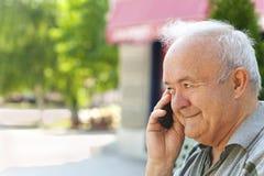 Uomo maggiore che comunica sul telefono Immagine Stock