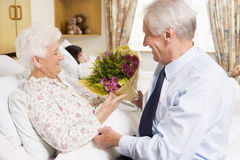 Uomo maggiore che dà i fiori alla sua moglie in ospedale Fotografia Stock Libera da Diritti