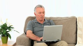 Uomo maggiore che lavora al suo computer portatile video d archivio