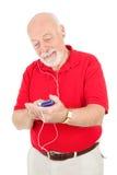 Uomo maggiore che per mezzo del giocatore MP3 Immagini Stock