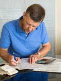 Uomo maggiore che prepara il modulo 1040 di imposta degli S.U.A. per 2012 Immagine Stock