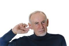 Uomo maggiore che pulisce fuori il suo orecchio immagini stock libere da diritti
