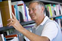 Uomo maggiore che tira un libro delle biblioteche fuori dalla mensola Immagine Stock