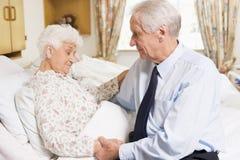 Uomo maggiore che visualizza la sua moglie in ospedale immagine stock