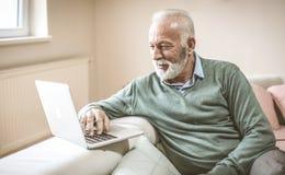 Uomo maggiore con il computer portatile fotografia stock