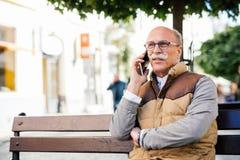 Uomo maggiore con il telefono mobile Tipo anziano con il fronte serio Ascolti me, il figlio Esprimere un parere saggio Immagine Stock