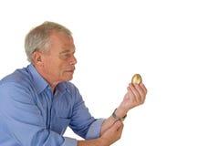Uomo maggiore con l'uovo dorato Fotografie Stock