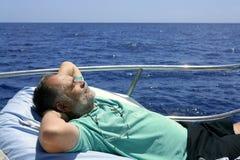 Uomo maggiore del marinaio che ha un resto sulla barca di estate Immagine Stock