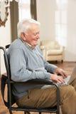 Uomo maggiore invalido che si siede in sedia a rotelle Fotografia Stock