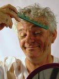 Uomo maggiore sporco che pettina i suoi capelli Immagine Stock Libera da Diritti