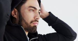 Uomo in maglia con cappuccio che posa contro il fondo bianco 4k stock footage