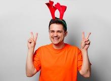 Uomo in maglietta arancio con i corni dei cervi di Natale fotografia stock