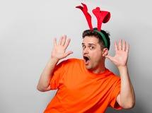 Uomo in maglietta arancio con i corni dei cervi di Natale immagini stock libere da diritti
