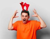 Uomo in maglietta arancio con i corni dei cervi di Natale immagini stock