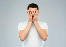 Uomo in maglietta bianca che copre il suo fronte di mani Immagini Stock Libere da Diritti