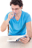 Uomo in maglietta blu con i vetri che si siedono alla tavola e che leggono la BO Fotografia Stock
