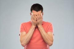 Uomo in maglietta che copre il suo fronte di mani Immagini Stock