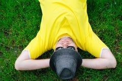 Uomo in maglietta gialla e cappello che si trovano sull'erba verde al parco fotografie stock libere da diritti