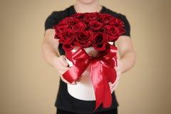Uomo in maglietta nera che tiene un mazzo ricco disponibile del regalo di rosso 21 Immagini Stock