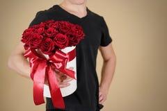 Uomo in maglietta nera che tiene un mazzo ricco disponibile del regalo di rosso 21 Immagine Stock Libera da Diritti