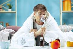 Uomo malato barbuto con il condotto di scarico che si siede sul sofà a casa Malattia, influenza, concetto di dolore Rilassamento  fotografie stock
