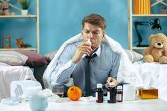 Uomo malato barbuto con il condotto di scarico che si siede sul sofà a casa Malattia, influenza, concetto di dolore Rilassamento  immagini stock libere da diritti
