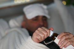 Uomo malato che apre una bottiglia dello sciroppo di tosse fotografia stock libera da diritti