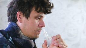 Uomo malato che inala attraverso l'ugello dell'inalatore per il naso Fronte del primo piano, vista laterale Utilizzi il nebulizza video d archivio