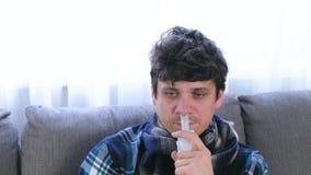 Uomo malato che inala attraverso l'ugello dell'inalatore per il naso che si siede sul sof? Fronte del primo piano, vista frontale stock footage