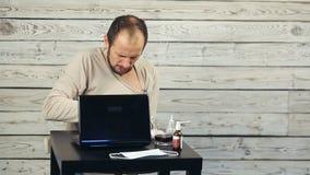 Uomo malato che lavora al computer video d archivio