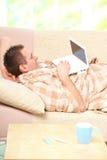 Uomo malato che pone sul sofà Fotografia Stock Libera da Diritti