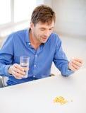 Uomo malato che prende le sue pillole a casa Fotografia Stock Libera da Diritti
