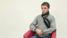 Uomo malato che si siede su una sedia che soffre dalla tosse video d archivio