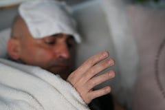 Uomo malato che si trova a letto immagine stock