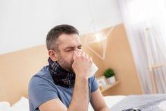 Uomo malato che soffia il suo radiatore anteriore Fotografie Stock