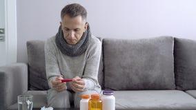 Uomo malato che tiene un termometro che si siede sullo strato Concetto medico e della gente di sanità, stock footage