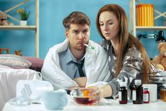 Uomo malato con febbre che si trova a letto facendo alla ragazza di temperatura prendere cura per lui fotografia stock libera da diritti