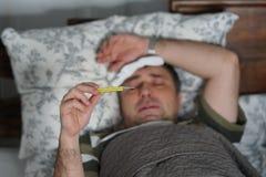 Uomo malato e stanco che si trova a letto controllando la sua temperatura fotografie stock libere da diritti