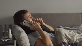 Uomo malato a letto accanto ai suoi farmaci nella sua casa che parla sul telefono Virus di sofferenza di influenza di freddo e di fotografia stock