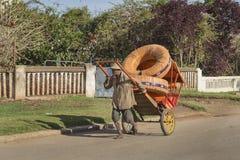 Uomo malgascio che tira un carretto rosso pesante Fotografia Stock Libera da Diritti