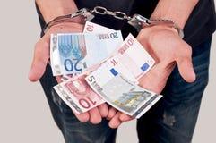 Uomo in manette che tengono soldi Immagine Stock Libera da Diritti