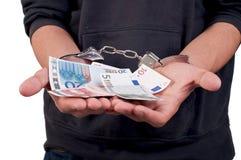 Uomo in manette che tengono soldi Fotografie Stock