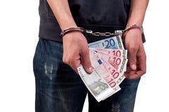 L'uomo in manette sta tenendo i soldi sopra fondo bianco Fotografia Stock Libera da Diritti