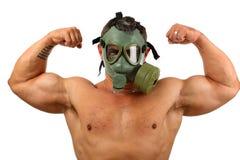 Uomo in maschera antigas che mostra i muscoli Immagine Stock