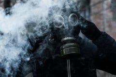 Uomo in maschera antigas contro il fondo di disastro Concetto di inquinamento immagini stock