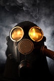 Uomo in maschera antigas sopra priorità bassa fumosa fotografia stock