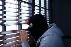 Uomo mascherato che spia attraverso i ciechi di finestra all'interno immagini stock libere da diritti