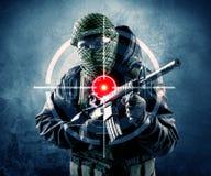 Uomo mascherato del terrorista con l'obiettivo di laser e della pistola sul suo corpo Fotografia Stock
