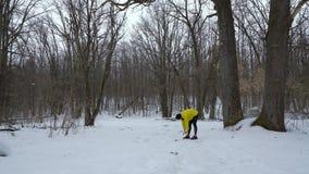 Uomo maschio di sport che si scalda durante le precipitazioni nevose nella foresta di inverno con spazio libero archivi video